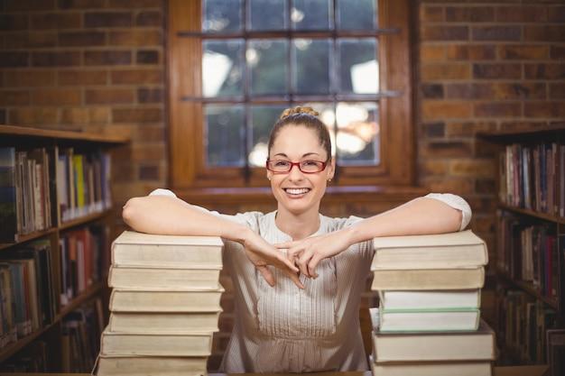 Loira professora permanente entre livros na biblioteca