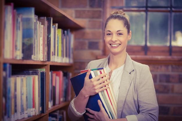 Loira professora segurando livros na biblioteca