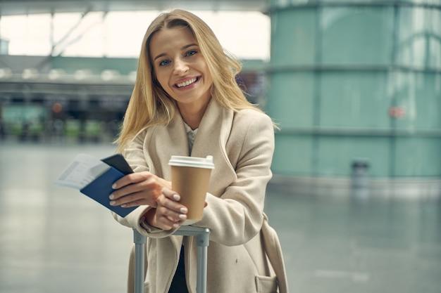 Loira satisfeita apoiando os cotovelos na mala enquanto vai beber um café aromático antes do voo