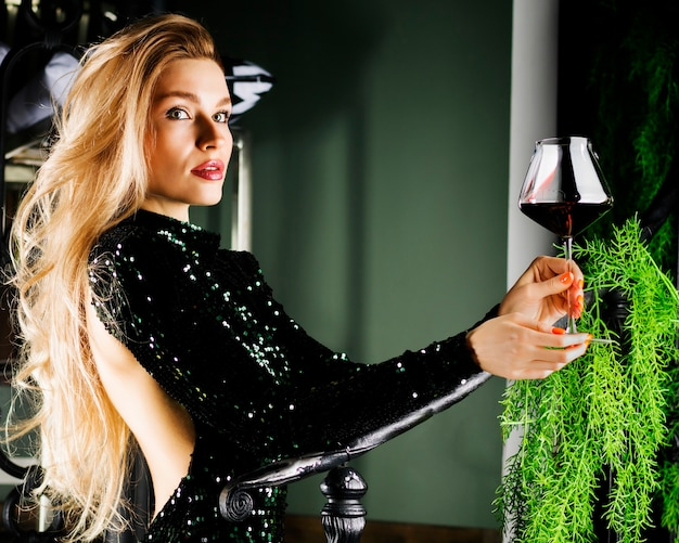 Loira sedutora em um vestido de noite verde, posando com uma taça de vinho tinto.