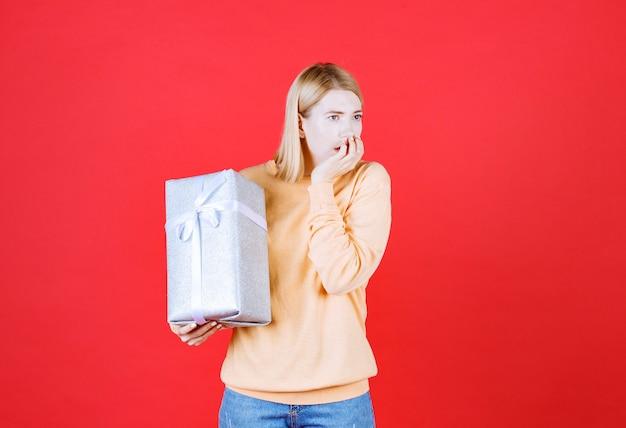 Loira segurando a caixa de presente enquanto coloca a mão perto da boca em frente à parede vermelha