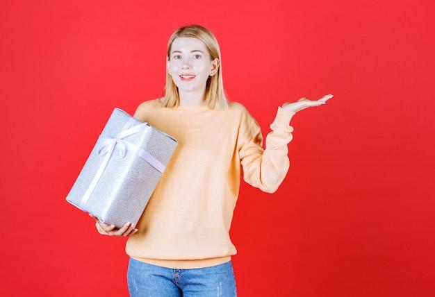 Loira segurando a caixa de presente enquanto faz um sinal com a mão na frente da parede vermelha