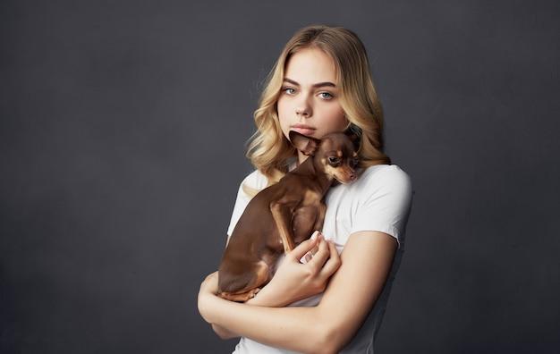 Loira segurando um close-up da amizade do animal de estimação do cão pequeno.