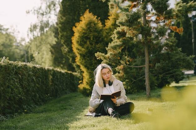Loira sentada em uma grama com fones de ouvido