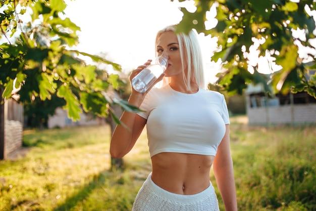 Loira sexy com uma camiseta molhada, de onde se vêem grandes seios, a garota derramou água sobre seus seios