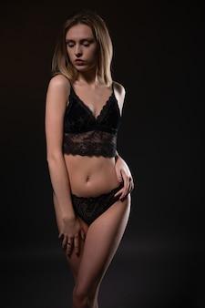 Loira sexy com uma figura linda em uma cueca de renda preta em uma luz contornada