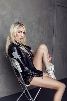 Loira sexy em cueca preta e uma jaqueta de couro se senta em uma cadeira perto da parede.