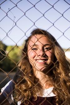 Loira sorridente através do elo da cadeia