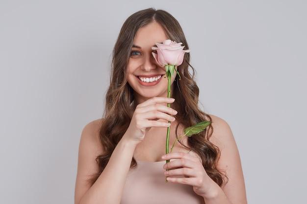 Loira sorridente com longos cachos, cobriu os olhos com uma rosa.