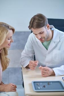 Loira sorridente examinando um aparelho surdo nas mãos de um jovem médico fofo