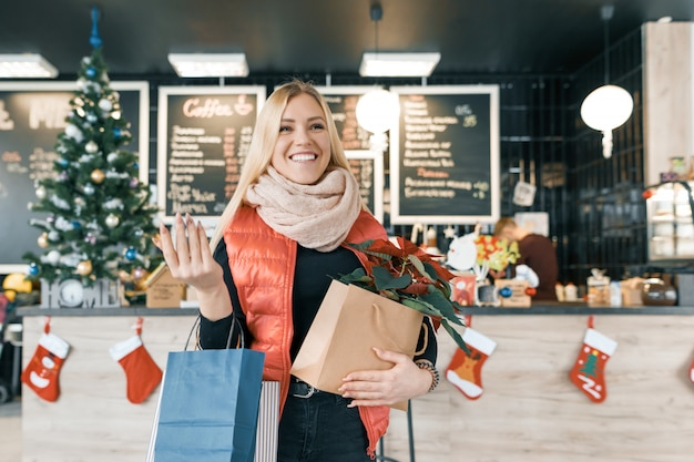 Loira sorridente feliz na cafeteria com sacolas de compras e flor de natal de poinsétia vermelha