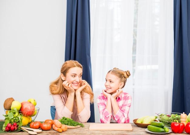 Loira sorridente mãe e sua filha olhando uns aos outros com legumes na mesa