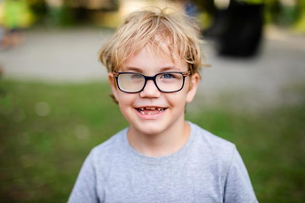 Loira sorridente menino com estrabismo usando óculos com lente especial no parque quente