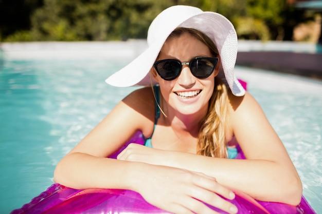 Loira sorridente no lilo na piscina