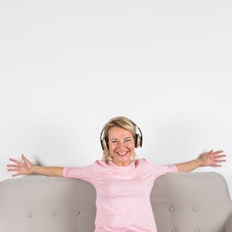 Loira sorridente retrato de uma mulher madura com fone de ouvido esticando os braços dela contra o fundo branco