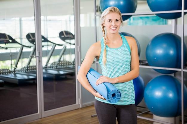Loira sorridente segurando o tapete de ioga no estúdio de fitness