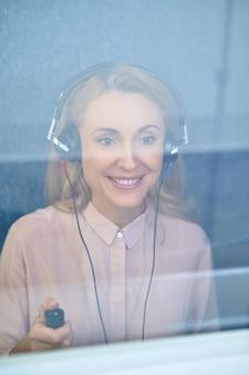Loira sorridente usando fones de ouvido na sala audiométrica