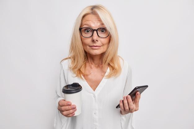 Loira surpresa, mulher de meia-idade, mensagens no smartphone enviando sms bebidas café para viagem usa óculos e blusa isolada na parede branca distraída do bate-papo online aproveita o tempo de lazer