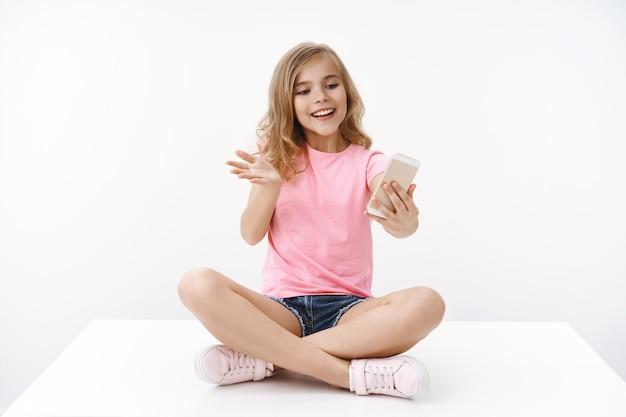 Loira terna alegre animada e entusiasmada jovem adolescente, sente-se com as pernas cruzadas, segure o smartphone, grave videoblog, torne-se blogueiro, gesticule animado explique a história falando amigo, parede branca