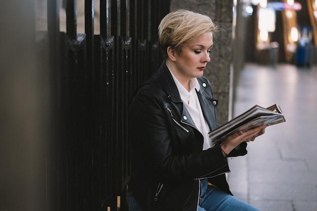 Loira vestindo jaqueta de couro sozinha na estação de metrô de são petersburgo lendo um livro