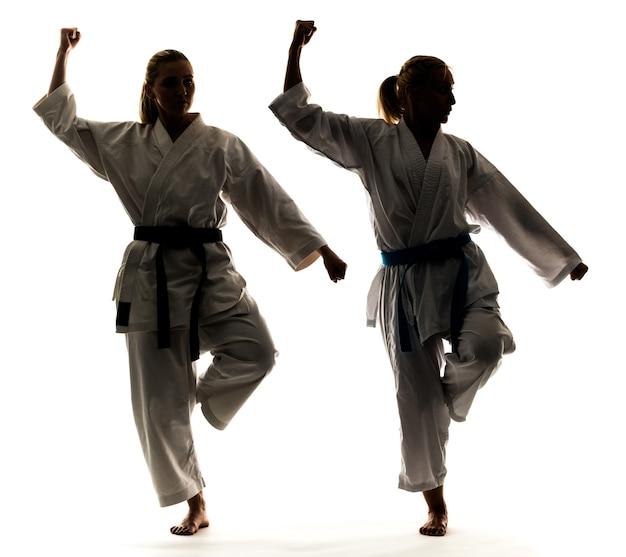 Loiras jovens e fortes estão treinando em um quimono em um fundo branco.