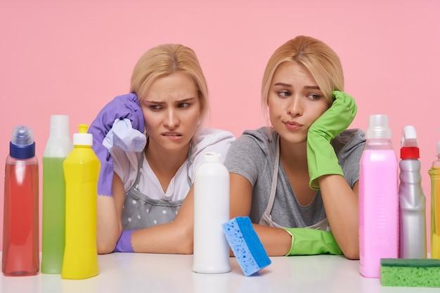 Loiras lindas donas de casa usando luvas de borracha enquanto se preparam para a limpeza de primavera