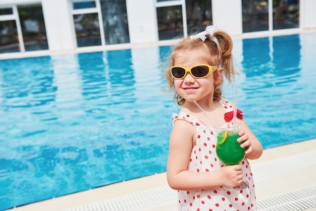 Loirinha bonitinha na piscina e segurando o coquetel de uma criança.