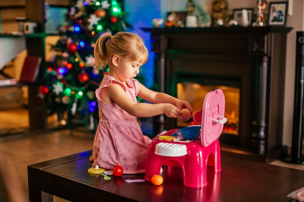 Loirinha brincando perto de árvore de natal com cozinha de brinquedo. manhã de natal na sala de estar decorada com lareira e árvore de natal.