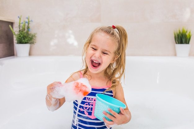 Loirinha engraçada tomando banho de espuma no banheiro bonito. shampoo, tratamento capilar e sabonete para crianças. copyspace.