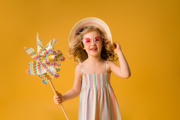 Loirinha sorri em um vestido de verão, óculos de sol, segurando o moinho de vento de uma criança em uma parede amarela