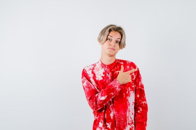 Loiro adolescente apontando para a direita em uma camisa grande e parecendo sombrio. vista frontal.