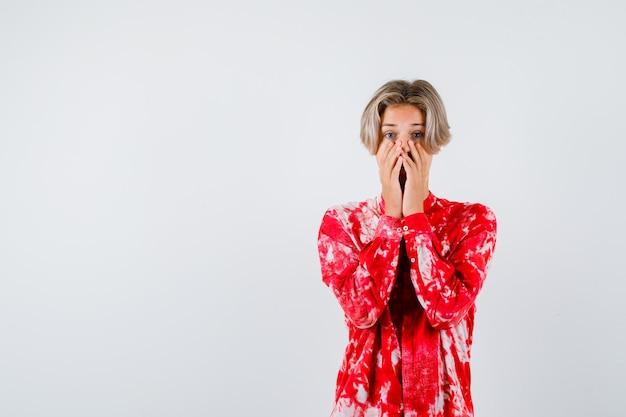 Loiro adolescente com as mãos no rosto em uma camisa grande e parecendo perplexo. vista frontal. Foto Premium