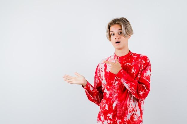 Loiro adolescente com uma camisa grande, apontando para a esquerda, mostrando um gesto de boas-vindas e parecendo perplexo, vista frontal.