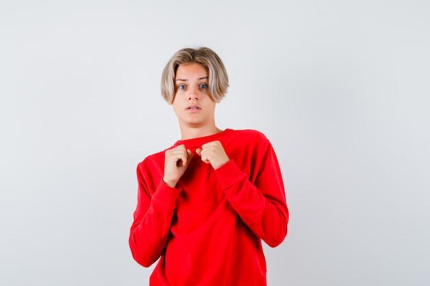 Loiro adolescente do sexo masculino no suéter vermelho em pé em pose de luta e olhando perplexo, vista frontal.