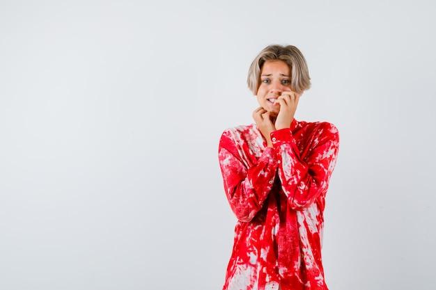 Loiro adolescente roendo as unhas em uma camisa grande e parecendo estressado, vista frontal.
