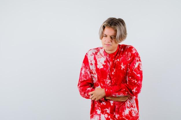 Loiro adolescente sofrendo de dor de estômago em uma camisa grande e parecendo dolorido. vista frontal.