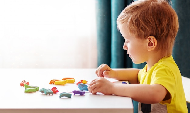Loiro bebê caucasiano esculpe de massa infantil para esculpir em casa à mesa, crianças e criatividade, o desenvolvimento de habilidades motoras finas