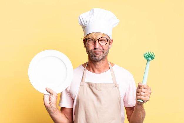Loiro bonito chef adulto homem com um prato vazio