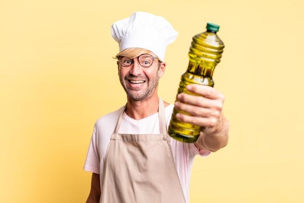 Loiro bonito chef adulto homem segurando uma garrafa de azeite
