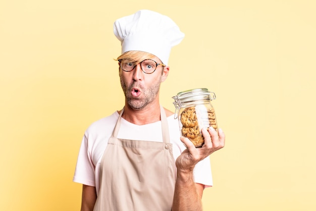 Loiro bonito chef adulto homem segurando uma garrafa de biscoitos caseiros