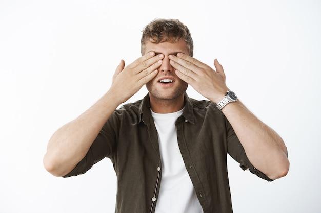 Loiro bonito fecha os olhos com as palmas das mãos e abre a boca em antecipação à espera da surpresa, ansioso para ver o presente posando curioso contra a parede cinza em uma camisa casual sobre uma camiseta