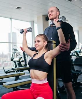Loiro cabe mulher no sportswear fazendo um haltere supino acima da cabeça enquanto está sentado em um banco com um instrutor parceiro masculino no ginásio