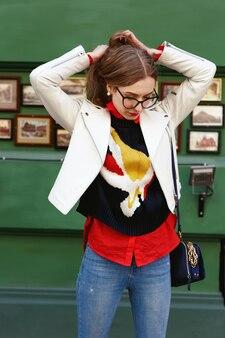 Loiro deslumbrante em óculos coloca em jaqueta branca na rua