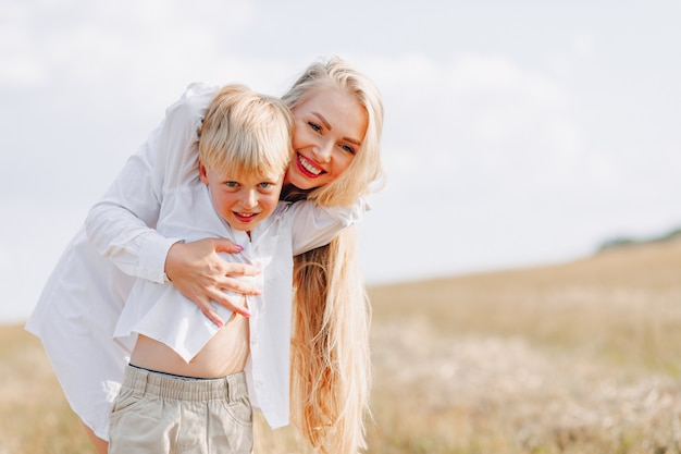 Loiro garoto jogando com a mãe com cabelos brancos com feno no campo. verão, tempo ensolarado, agricultura. infância feliz.