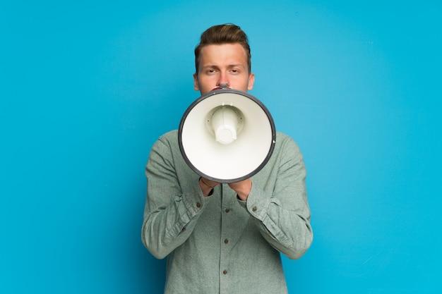 Loiro, homem, sobre, isolado, parede azul, shouting, através, um, megafone