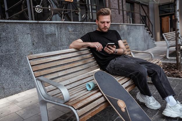 Loiro jovem e bonito usando a rolagem do smartphone, curtindo postagens e compartilhando-as nas redes sociais, trocando mensagens, lendo notícias sentado no banco com longboard, concentrado, sério