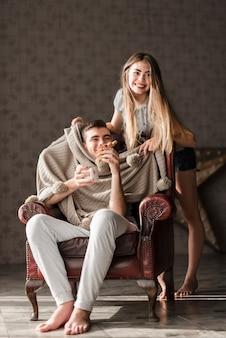 Loiro, jovem, mulher, ficar, perto, a, homem, comer, croissant, e, segurando, xícara café