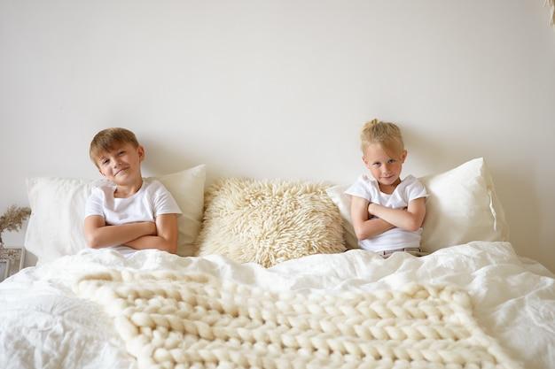 Loiro menino bonitinho relaxando no quarto, sentado na cama com seu irmão mais velho, ambos mantendo os braços cruzados e olhando para a câmera e sorrindo. conceito de crianças, roupa de cama e hora de dormir
