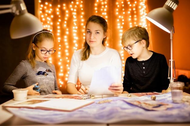 Loiro menino e menina e sua mãe escreve a carta para o papai noel