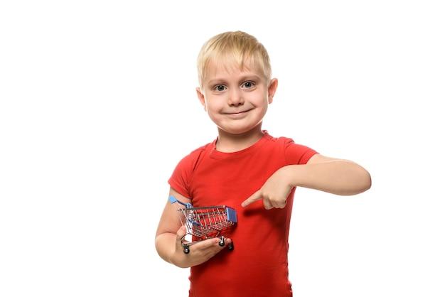 Loiro menino sorridente em uma camiseta vermelha, segurando um pequeno carrinho de compras de metal e apontando para ele com o dedo indicador
